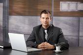 Bem parecido confiante gerente sentado no escritório de fantasia, sorrindo.?