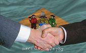 Delante de la bandera del Estado americano de apretón de manos de dos hombres de negocios Delaware después de mucho