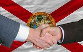Delante de la bandera del Estado americano de Florida dos empresarios apretón de manos después de mucho