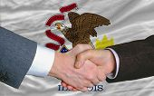 Delante de la bandera del Estado americano de apretón de manos de dos hombres de negocios Illinois después de mucho