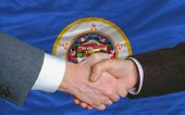 In Front Of American State Flag Of Minnesota Two Businessmen Handshake After Good Deal