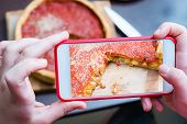 Top View Of Chicago Pizza. Woman Hands Taking Photo With Smart Phone Of Chicago Style Deep Dish Ital poster