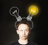 Man With Light Bulb On Blackboard Background. Brainstorming And Idea Concept poster