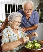 Happy senior couple preparing vegetable salad in the kitchen. Grandparents at kitchen preparing vege