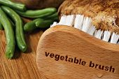 Wooden vegetable brush (with words engraved) on cutting board with wet potatoes and green beans.   Macro with shallow dof.  Food safety concept.