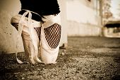 stock photo of ballet shoes  - Tattered ballet shoes on a gravel road with fishnet stalkings - JPG