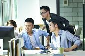Four Young Asian Corporate Executives Working Together Discussing Business Plan Using Desktop Comput poster