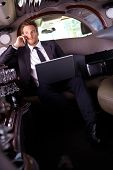 Handsome young businessman sitting in limousine, talking on mobile phone, using laptop computer.?