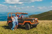 Young Family Posing Near Suv Car With Beautiful View Of Mountains. Travel Concept poster
