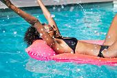 Happy young fashion woman in bikini with rubber inflatable float and having fun with water at swimmi poster