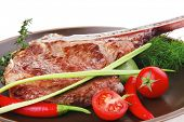 meat food : grilled beef spare rib on dark dish with thyme pepper and tomato isolated over white background