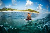 Surfer rides the ocean wave at sunset. Honkeys surf spot in the Maldives poster