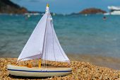 Wooden toy sail boat at the beach