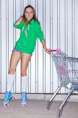 una hermosa joven en rodillo scates junto a la carretilla del supermercado