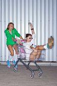 dos niñas hermosas con un skateboard, rodillo scates y un carrito de supermercado