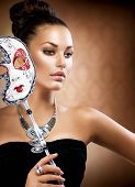 Masquerade Woman. Beauty Girl with Carnival Mask. Holiday Dress and Makeup. Fashion Brunette Portrai