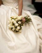 bride holding white rose bouquet shot with tilt-shift lens
