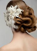 Portrait of attractive young woman with beautiful hairstyle and stylish hair decoration. Bride with