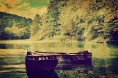 Lake and two boats in forest. Retro vintage romantic syle