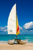 Catamaran with its colorful sail spread out on Varadero beach in Cuba