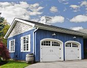 image of quaint  - Double car garage with white doors and blue exterior - JPG