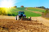 picture of cultivator-harrow  - Tractor plows a field in the spring with sunlight - JPG