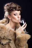 Gorgeous woman in luxurious fur coat drinking wine