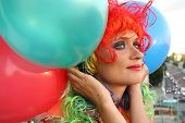 Girl in colorful wig with balloons