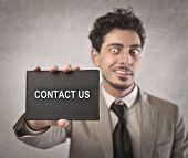Empresário segurando um cartão preto em que está escrito entre em contato conosco