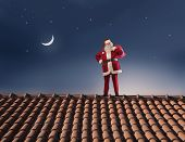 Santa Claus on the roof of a house with his sack full of presents
