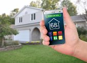 picture of temperature  - A smart phone is in front of a house with various home control icons like temperature and time - JPG