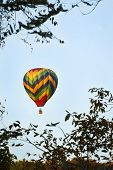 Colorful hot air balloon ascending against a blue sky