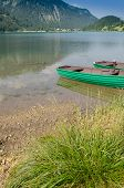 stock photo of u-boat  - Lake in Tirol with green wooden boats in vertical format - JPG
