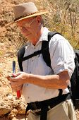 stock photo of paleontologist  - Senior geologist tap a rock formation with a hammer - JPG