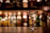 foto of bartender  - a cup of martini with olive on a old pub