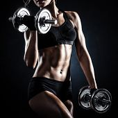 stock photo of muscle  - Brutal athletic woman pumping up muscles with dumbbells - JPG
