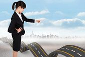 Focused businesswoman pointing against bumpy road backdrop
