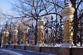The fence of the city park on a cold day in winter