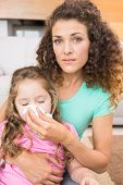 Worried mother helping her little daughter blow her nose at home in living room