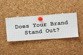 image of reminder  - The phrase Does Your Brand Stand Out typed on a piece of graph paper and pinned to a cork notice board - JPG