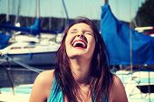 Happy girl in front of yacht boat is laughing with closed eyes. Beautiful young woman with dispelled hair in yacht harbor.