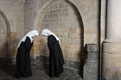 Two nuns greeting eachother inside a medieval abbey