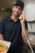 Happy pizza delivery man taking an order over the phone in a commercial kitchen