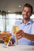 Happy businessman clinking glass of beer with bartender in a bar