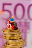woman in wheelchair on money stack, symbol photo for disability care allowance and costs gesunheitsw