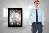 Smiling businessman standing with hand in pocket against bright room with opened windows
