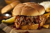 stock photo of pork  - Barbeque Pulled Pork Sandwich with BBQ Sauce and Fries - JPG