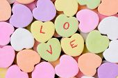 Macro shot of pastel candy hearts for Valentine's Day. Four of the candies have the word LOVE spelle