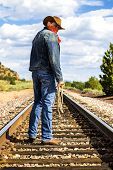 picture of track field  - Cowboy with boots and hat and bandana crosses train tracks