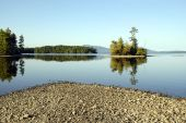 pic of moosehead  - Early Autumn leaves from trees on a small island reflected in the calm waters of Moosehead Lake in northern Maine - JPG